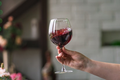 Hand sommelier holding glass of red wine. Swirling red wine glass in wine tastings. Wine tour. Space for text.