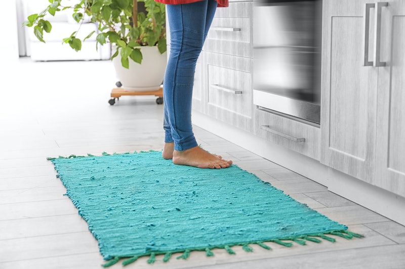 Woman standing on rug in kitchen