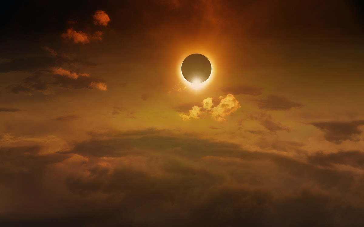 Amazing scientific background - total solar eclipse in dark red glowing sky, mysterious natural phenomenon when Moon passes between planet Earth and Sun