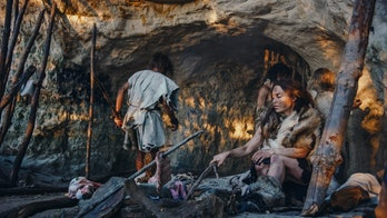 Tribe of Hunter-Gatherers Wearing Animal Skin Live in a Cave. Leader Brings Animal Prey from Hunting, Female Cooks Food on Bonfire, Girl Drawing on Wals Creating Art. Neanderthal Homo Sapiens Family