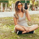 Young beautiful woman enjoying the music at outdoor park. Woman listening music by wireless speaker at outdoor park