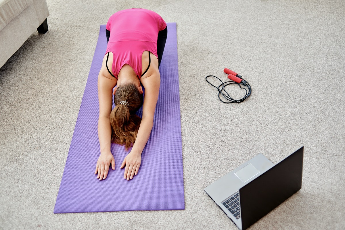 Beautiful young woman doing stretching exercise on floor at home, online training on laptop computer...
