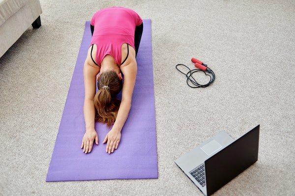 Beautiful young woman doing stretching exercise on floor at home, online training on laptop computer, copy space. Full length portrait. Yoga, pilates, working out exercising