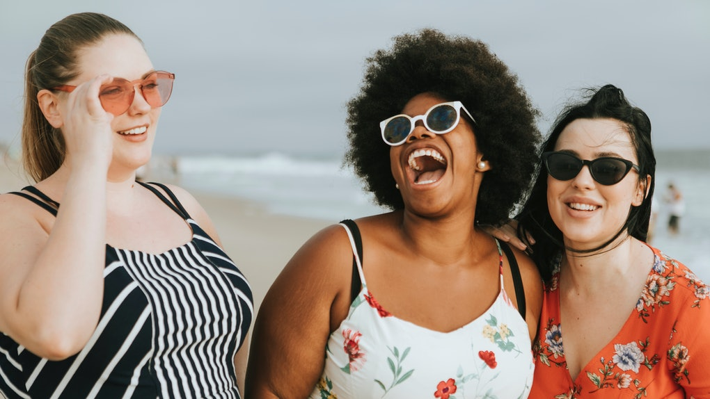 Three happy friends laugh while standing on the beach on a summer day.