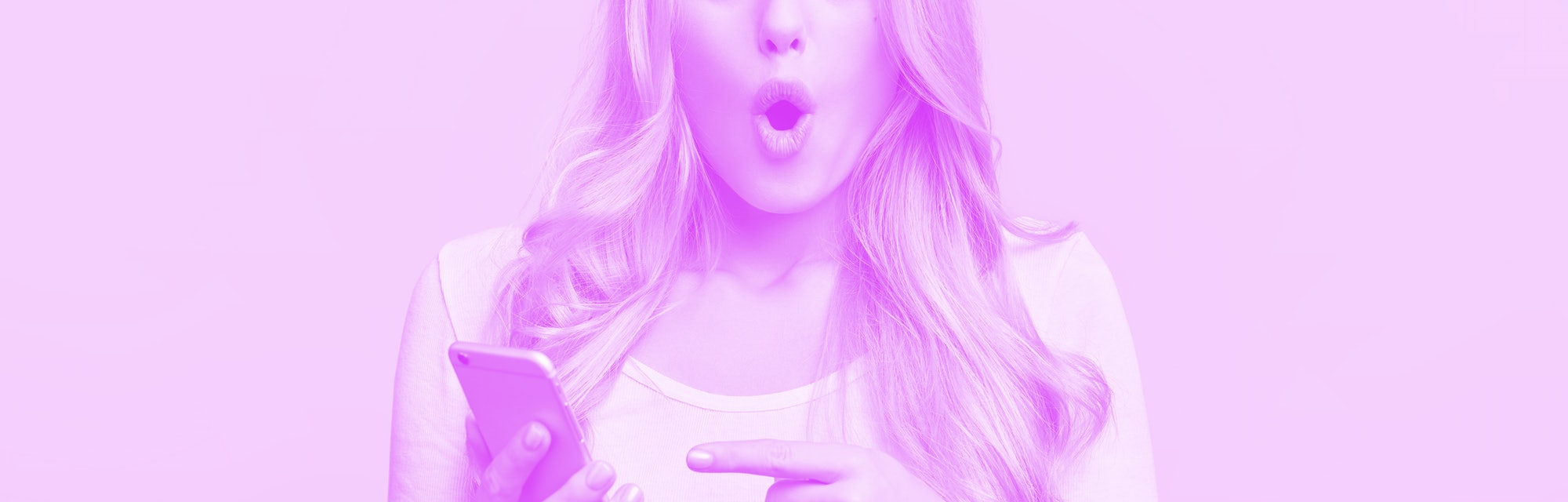 Blonde young female with pleasant appearance looks with terrified expression in smart phone, reads shocking news on webpage, isolated over pink background. Woman indicates at digital telephone