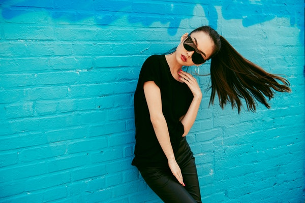 Beautiful young asian girl with long hair wearing sunglasses and black t-shirt posing in front of blue wall