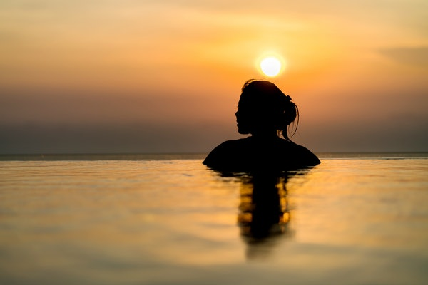 Black silhouette of asian woman on summer vacation holiday relaxing in infinity swimming pool with blue sea sunset view. Healthy happiness lifestyle