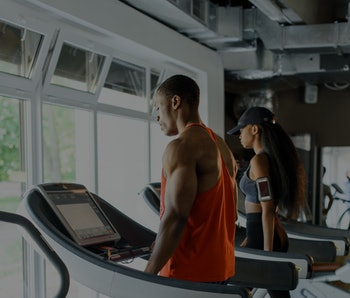 Black african american athletic couple running on treadmills in gym
