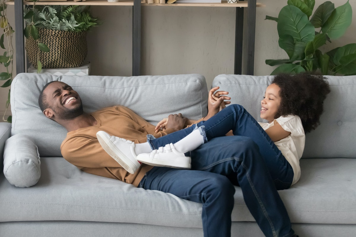 A father and daughter laugh and smile on the couch.