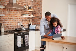 Father And Daughter Using Digital Tablet In Kitchen At Home