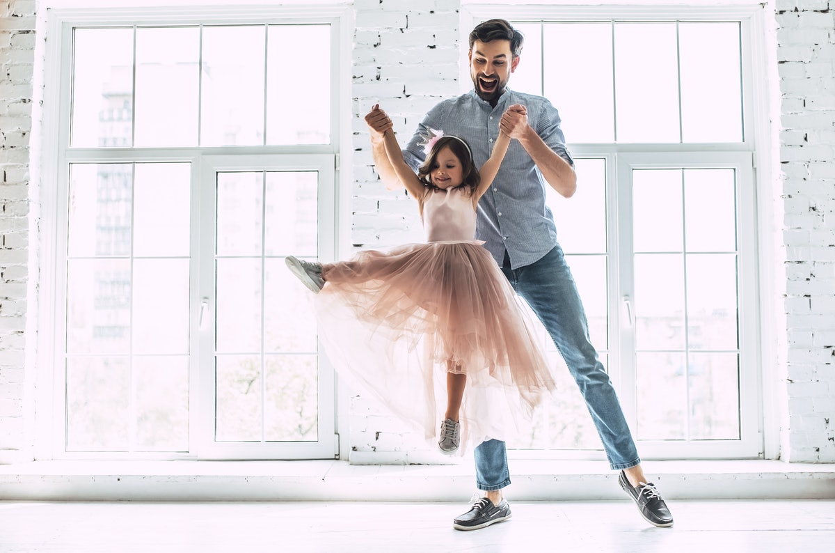 A younger father dressed in jeans and a button-down shirt laughs while he lifts his ballerina daughter up as she points her foot out.