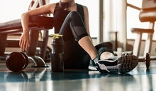 Fitness woman Relaxing after exercise with a whey protein and dumbbell placed beside the gym.Relaxi...