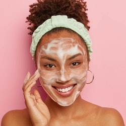 Happy dark skinned woman pampers face with bubble cleansing foam, has hygienic treatments in bathroo...