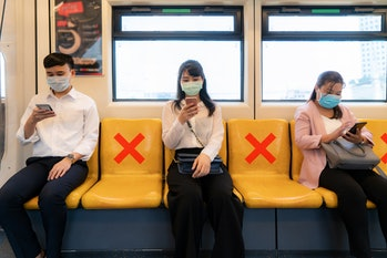 Three Asian people wearing mask sitting in subway distance for one seat from other people keep dista...