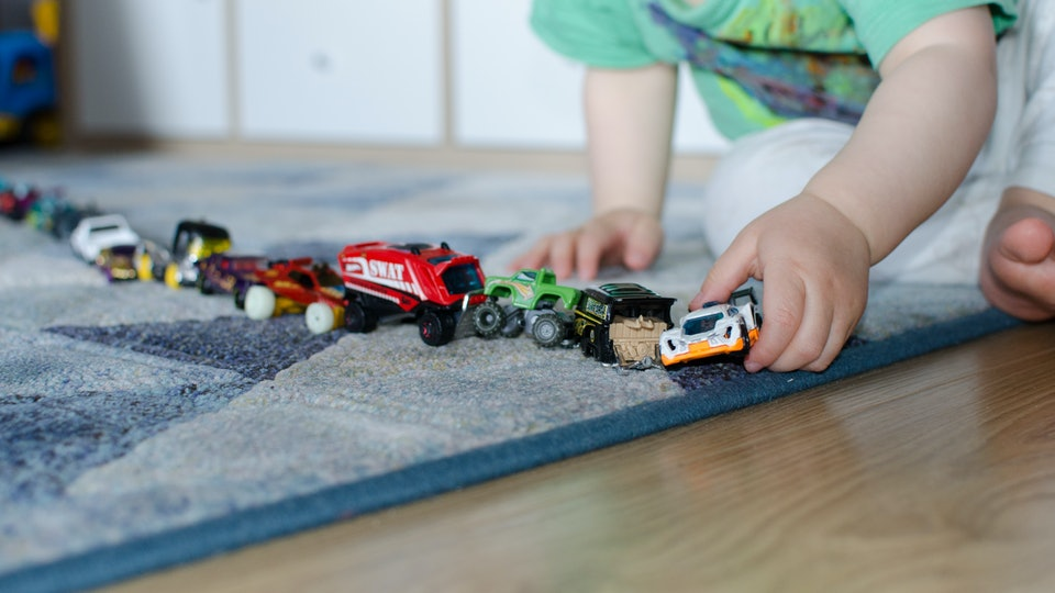 Child lining up toys on the floor at home.