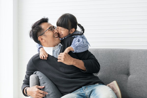 An Asian father and daughter laugh while snuggling on the couch in their living room.