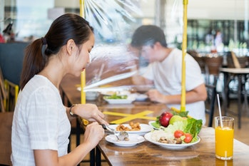 Asian man and woman sitting separated in restaurant eating food with table shield plastic partition ...