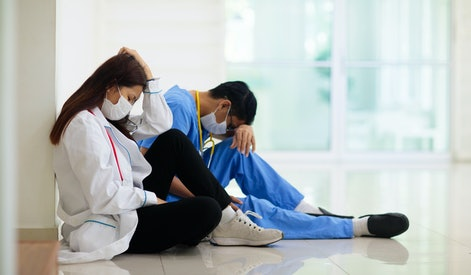 Exhausted tired Asian doctor or nurse. Virus outbreak in Asia. Coronavirus pandemic. Clinic and hospital medical stuff working over hours. Overworked professional. Stress and depression.