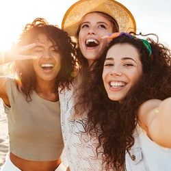Three happy friends pose for selfie on the beach during the summer.