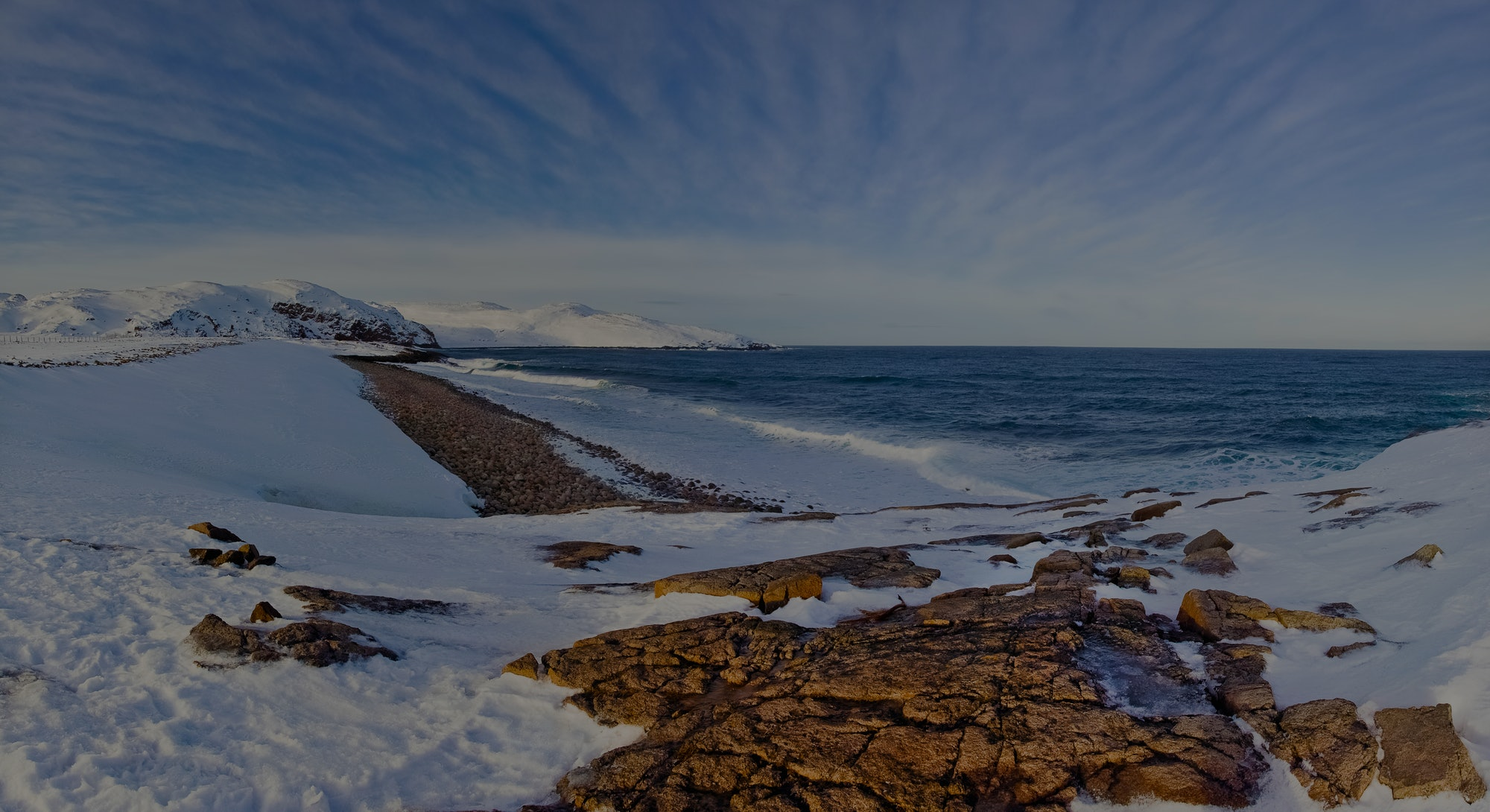 Winter storm in a sunny day in the Arctic Ocean, the Barents Sea, the settlement of Teriberka, Russia. A severe northern cold landscape with the sea, snow and stones.