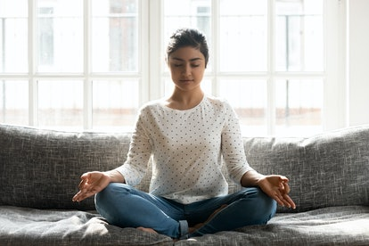 Full length mindful young indian woman making mudra gesture, sitting in lotus position on comfortabl...