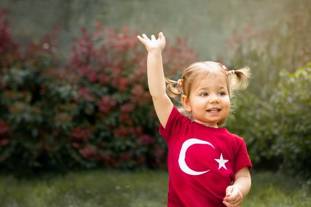 Portrait of happy little kid, cute baby toddler with Turkish flag t-shirt wave her hand. Patriotic holiday. Adorable child celebrates national holidays. Blur background with copy space for text.