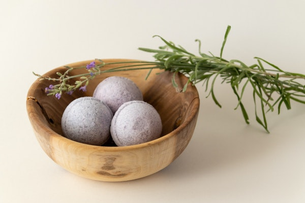 Lavender bath bombs in a wooden bowl with lavender cuttings