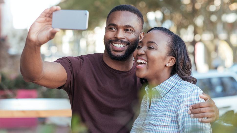 Laughing young African couple taking a selfie together at a sidewalk cafe table while out on a date