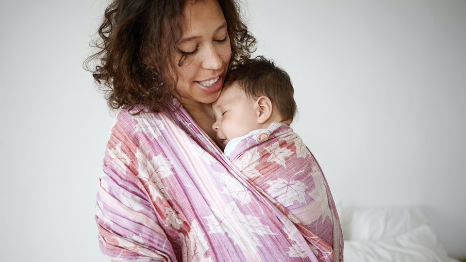 Indoor shot of beautiful young mixed race mother smiling, watching her adorable newborn infant son sleeping peacefully in baby sling, her look full of love. Parenting, babywear and childcare concept