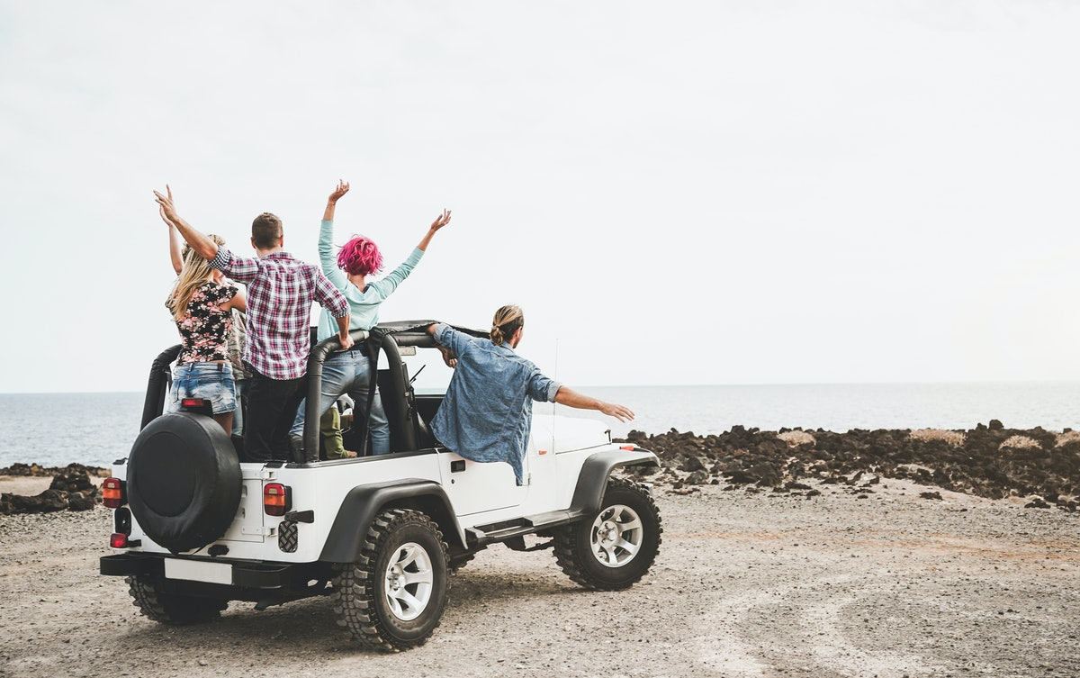 A group of friends in a Jeep Wrangler throw their hands in the air while parked near the shore.