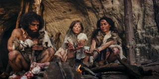 Tribe of Prehistoric Hunter-Gatherers Wearing Animal Skins Live in a Cave at Night. Neanderthal or H...