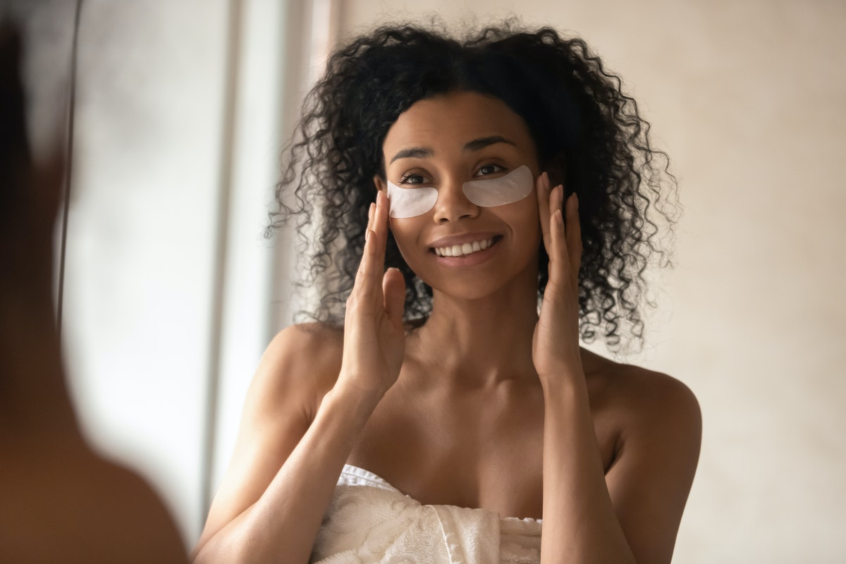 A woman in a bath towel puts under-eye patches while working on her skincare.