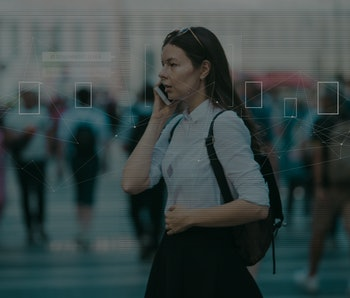 Facial recognition and search and surveillance of a person in the modern digital age, the concept. Young woman with phone in crowd of people on the street, identification and modern technology