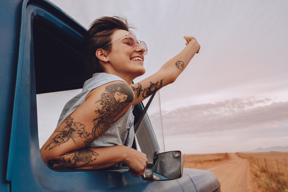 Shot of attractive young woman enjoying road trip on a summer day. Happy young female raising her hand out of the car window.