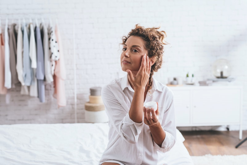 Pretty smiling Caucasian woman applying a skin cream to her face during her morning routine.