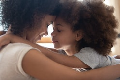 Close up head shot side view calm happy mixed race mother cuddling little cute daughter, touching fo...