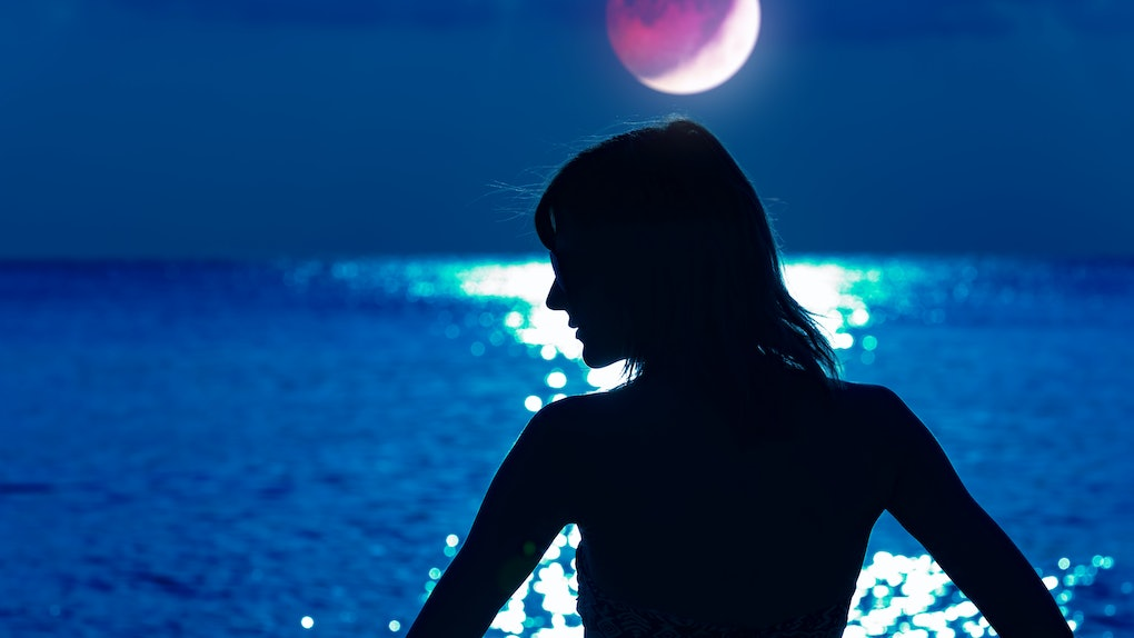 Silhouette of a woman with distant ocean horizon at night.