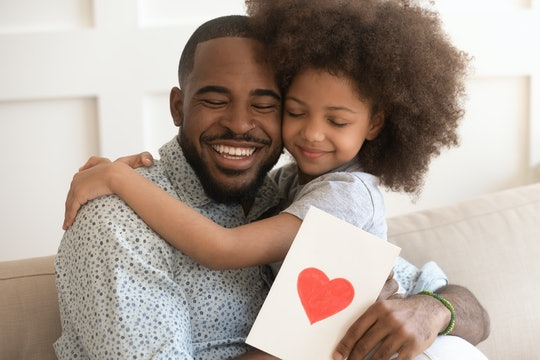 Happy affectionate african american dad embracing little child daughter holding greeting card with red heart bonding on fathers day concept, smiling cute kid girl hug daddy congratulate make surprise