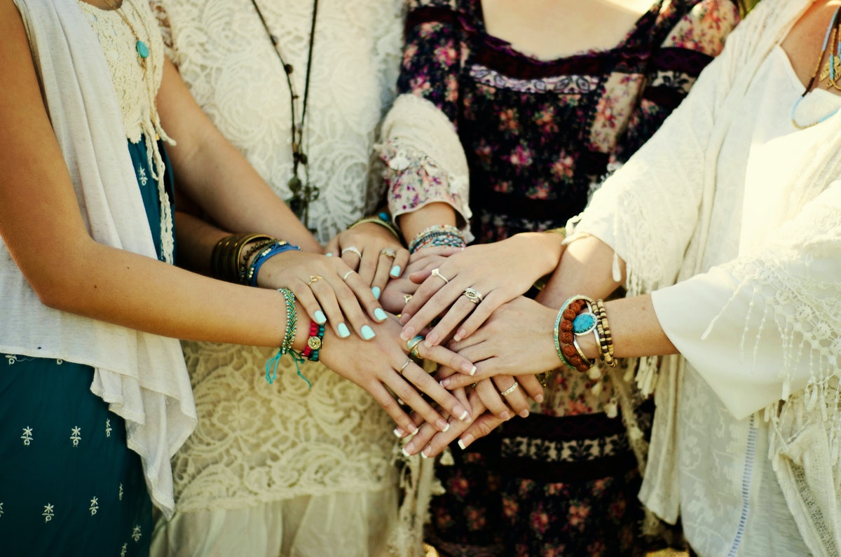 A group of woman wearing boho outfits and friendship bracelets form a circle and join their hands together in the middle.