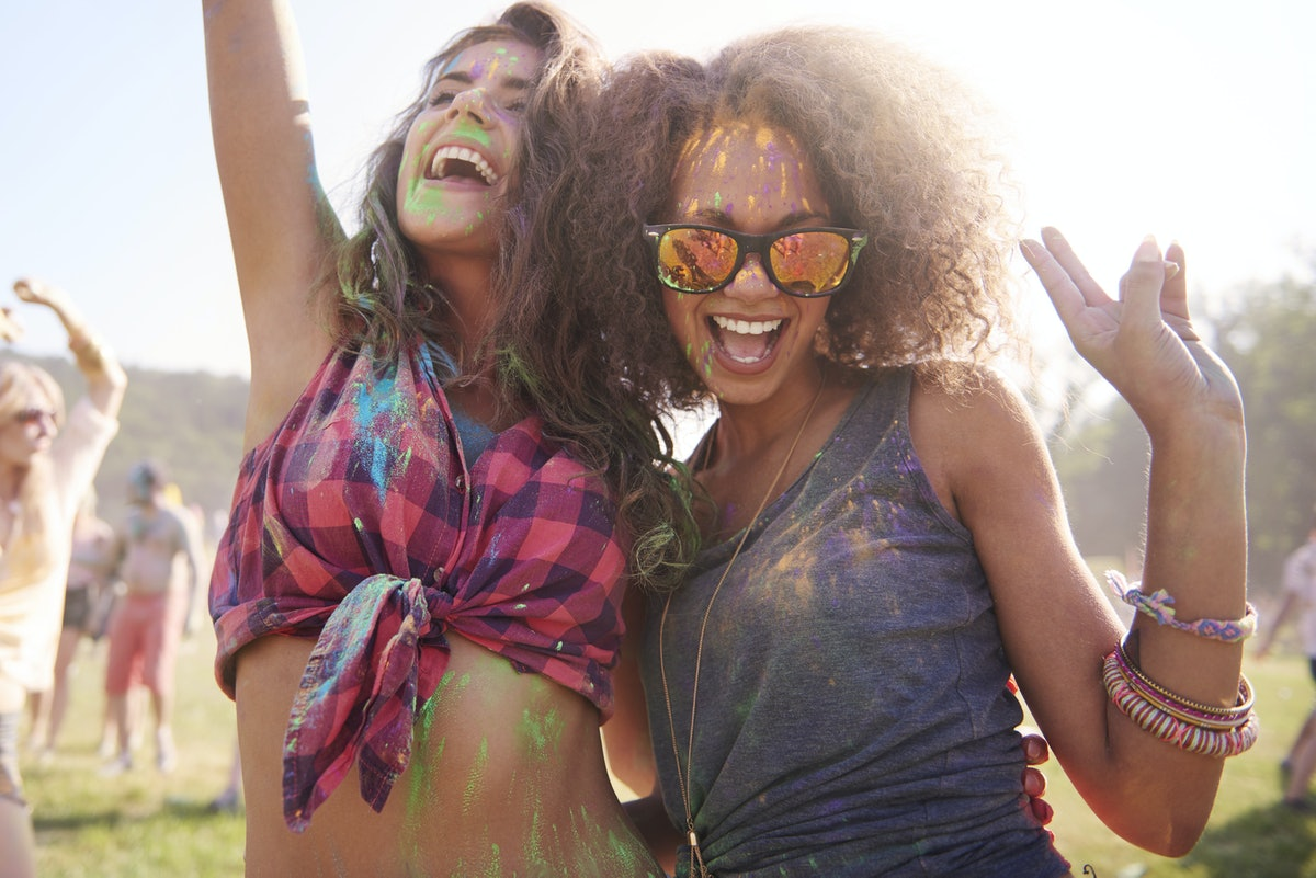 A happy woman with friendship bracelets and sunglasses, dances at an outdoor festival with her friend.