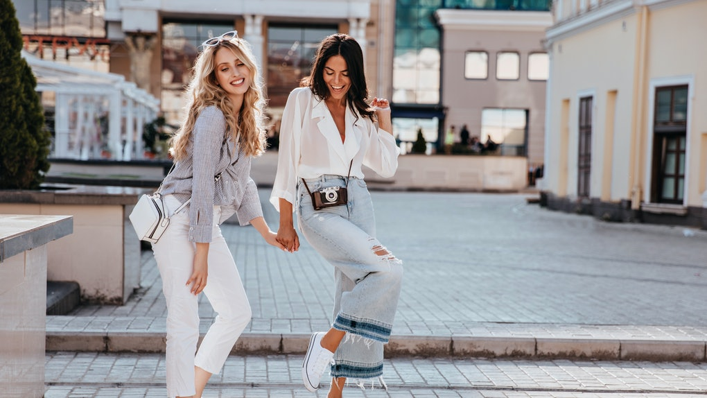 Two friends wearing jeans, trendy tops, and white sneakers hold hands and strike a pose on a sidewalk.
