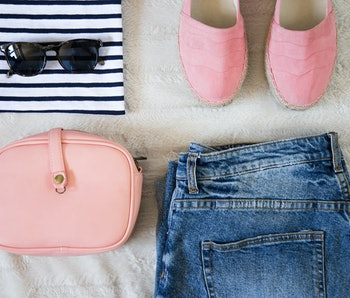 flat lay women fashion. trendy hipster clothes, accessories top view. fashion bloggers outfit collage with jeans, striped t-shirt, pink espadrilles shoes, bag and sunglasses. perfect summer outfit.