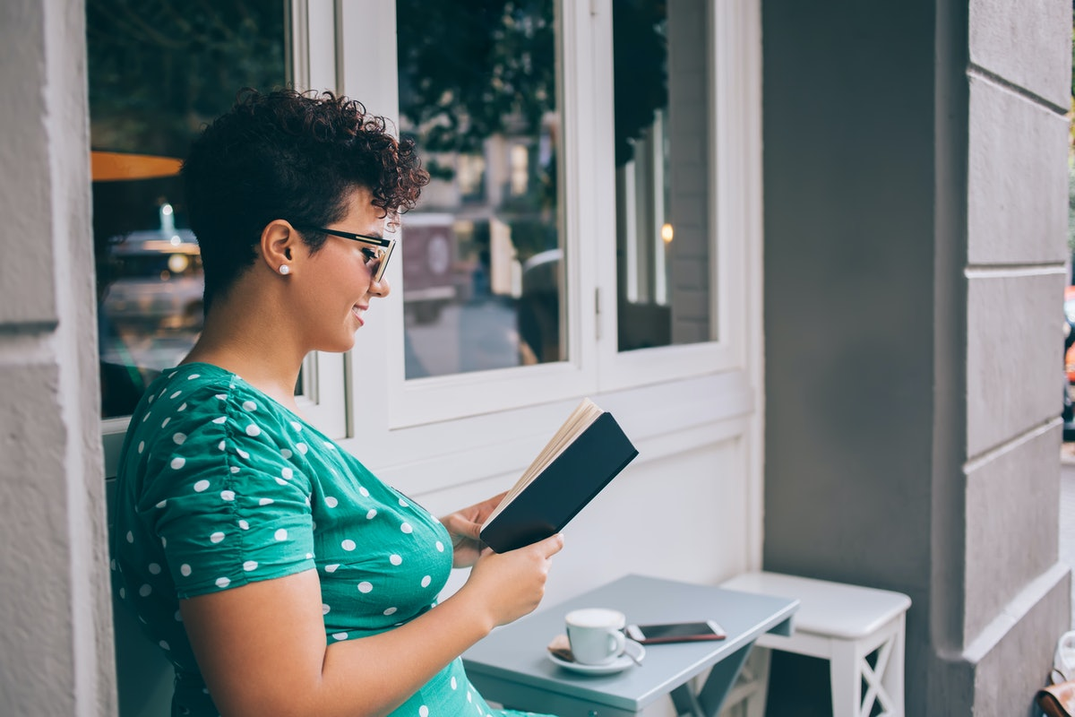 Side view of happy woman in glasses interested on literature plot during leisure time in street cafeteria for reading favourite best seller, prosperous female reader enjoying education hobby with book
