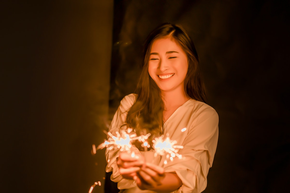 Asian woman holding bright festive Christmas sparkler in hand,firework pyrotechnics and bokeh on the dark background for celebration concept