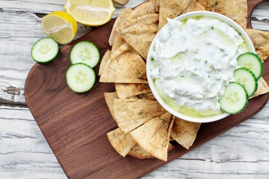 Traditional Greek Tzatziki dip sauce made with cucumber sour cream, Greek yogurt, lemon juice, olive oil and a fresh sprig of dill weed. Served with toasted Za'atar Pita bread.  Top view  or flat lay.
