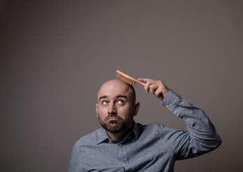 caucasian confused bald man trying hair brush