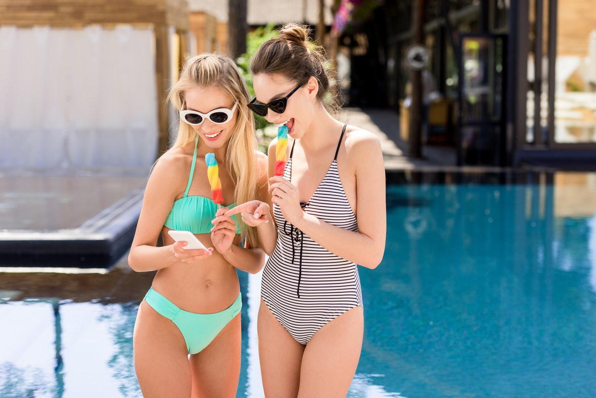 Two happy friends eating popsicles by the pool, look at their phones.