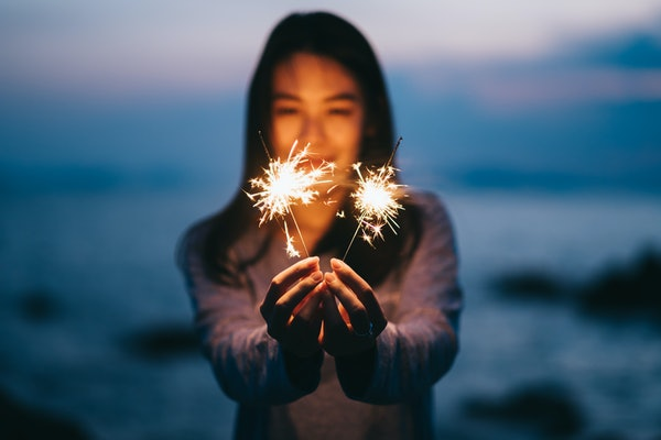 Young happy woman stands on beach with sparkler in sunset light.