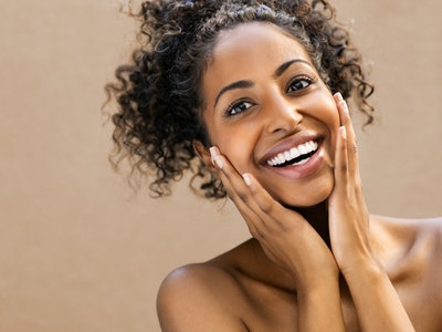 Beautiful young woman smiling after fantastic face treatment. Happy beauty african girl excited after spa treatment isolated on background with copy space. Surpise and astonishment beauty concept.