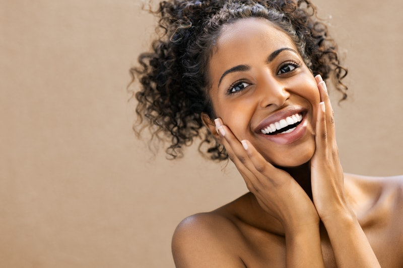 Beautiful young woman smiling after fantastic face treatment. Happy beauty african girl excited afte...